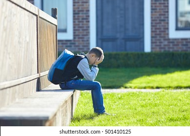 schoolboy crying in the yard of the school, negative emotion