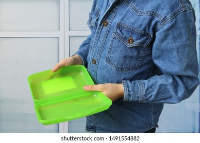 schoolboy in a denim jacket holds an empty plastic lunchbox in his hands, a concept of poor nutrition