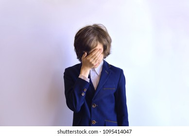The schoolboy is in despair. The schoolboy is crying. Schoolboy in uniform with closed face on a white background