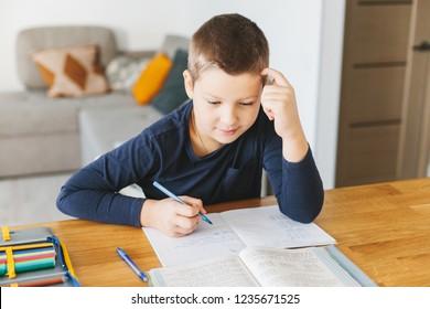 Schoolboy doing his homework on desk at home. Homeschooling concept