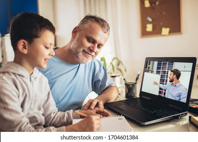 Schoolboy educate online. Father helps his son with home work. Boy in video conference with teacher on laptop at home.