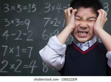 Schoolboy in front of blackboard holding head
