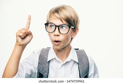 Schoolboy in glasses shows forefinger up as he has an idea