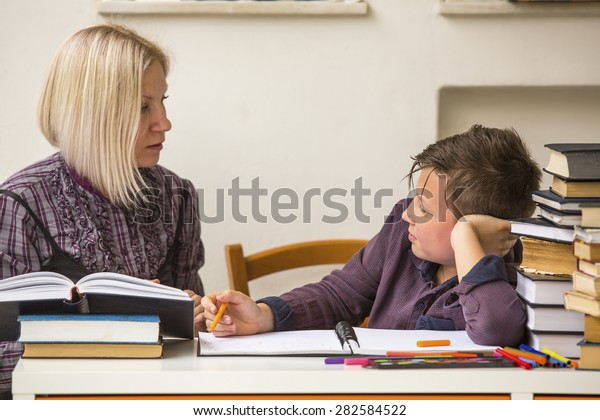 Schoolboy with his tutor do homework.