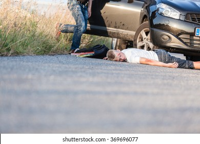 Schoolboy Hit by a Vehicle, Lying on the Road Wounded and the Car Owner Running Towards Him for Help.