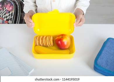 The schoolboy holding a yellow plastic box with lunch in school.  In the box are a banana, apple and a biscuit,  there is a pencil box and notebooks nearby