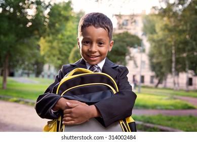 Schoolboy hug his bag