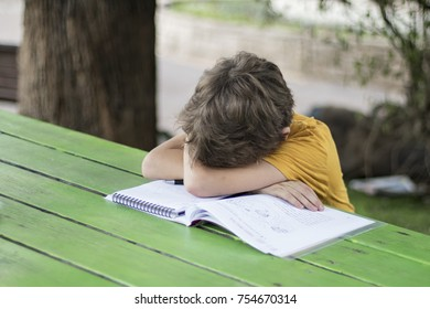 The schoolboy laid his head on the open notebook with his homework and wrapped it around his arms