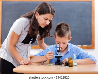 Schoolboy looking inot microscope while the biology teacher is attending him