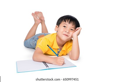 Schoolboy lying on a floor, looking up and writing in notebook.
