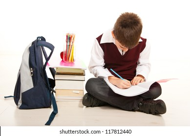 Schoolboy making homework and sitting with legs crossed on the floor isolated on white background