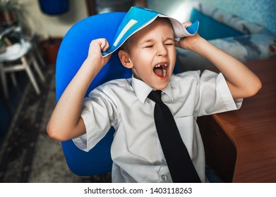 Schoolboy with a notebook on his head tired of learning. The boy learns lessons. Schoolboy doing homework. The boy is preparing for school. The boy does not want to learn lessons. Home schooling