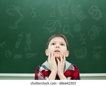 Schoolboy on the background of a board with drawings and formulas