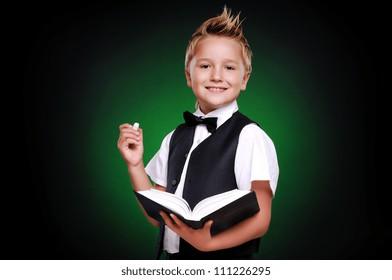 Schoolboy on green school board background