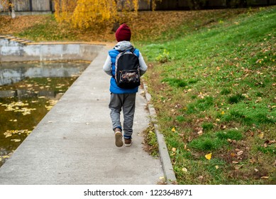 Schoolboy on his way to the home. Boy going to the class in his school. Handsome cool mixed schoolboy with notes and books in his hands on the school garden. Children and education in the city.