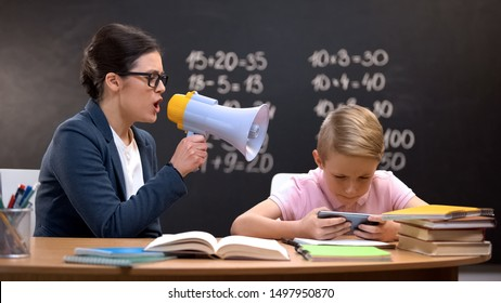 Schoolboy playing game on phone, teacher shouting in megaphone, naughtiness
