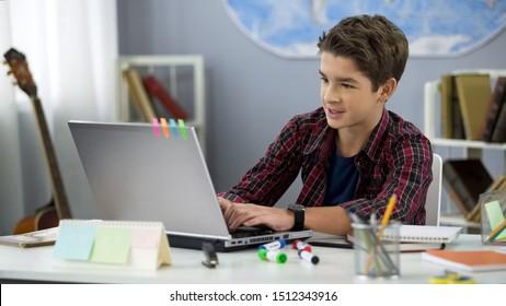 Schoolboy, der auf dem Laptop zu Hause sitzt, Freizeit für Teenager