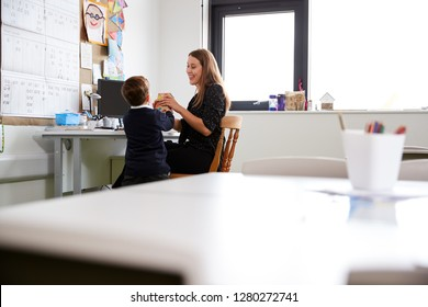 Schoolboy at primary school presenting a gift to his female teacher in a classroom, selective focus, back view