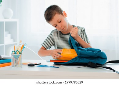 schoolboy putting school stationery into backpack at table indoors at home white room. preparation for school, homework - Shutterstock ID 1999795529