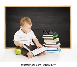 Schoolboy reading book near blackboard, kindergarten school boy, little child on black board background, elementary education concept