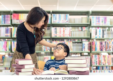 Schoolboy reading books for education and go to school with the guidance of his teacher in library . Education and Lifestyle Concept