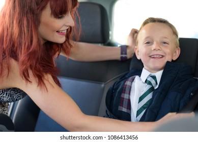 Schoolboy sat in car seat, ready to go back to school