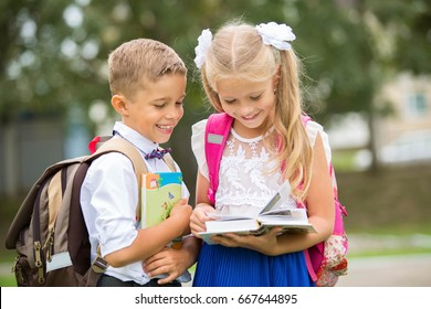 Schoolboy and schoolgirl looking into a book and smiling