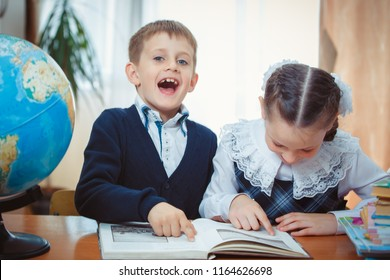 A schoolboy and a schoolgirl are sitting at a desk. The schoolgirl points a finger at the book, and the schoolboy looks