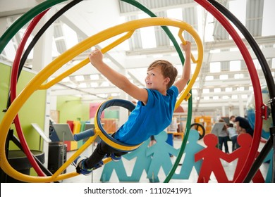 Schoolboy in science centre using human gyroscope, side view