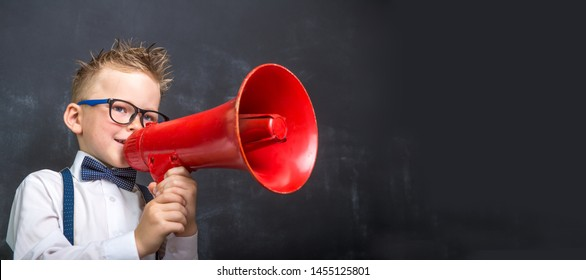 Schoolboy shouting through loudspeaker. Pupil from primary school  shouting in retro vintage red megaphone. Communication in education. Back to school.