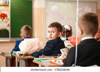 schoolboy sits at a Desk at school on September 1.Holiday of knowledge. The child goes to school for the first time.Back to school. Concept of school education. Rear view. Selective focus on the chil