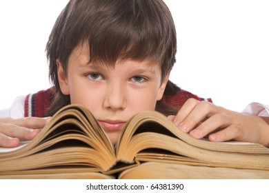schoolboy sitting at the table with big book