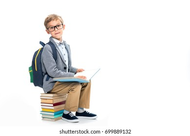 schoolboy sittting on stack of books and reading isolated on white