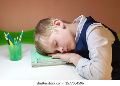 A schoolboy is sleeping on notebooks. The child lies on the table. Many homeworks or exam is stress for little kids. Heavy school program. Studying, fatigue, overwork, preparation, education concept.