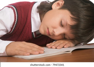 schoolboy sleeping on the table with notebook