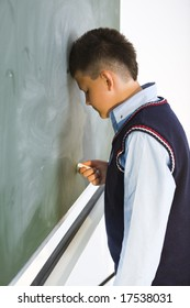 Schoolboy standing at chalkboard and holding chalk in hand. Side view.