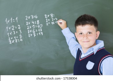 Schoolboy standing and writing something on chalkboard. He's looking at camera.