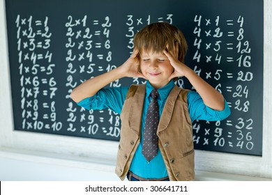 Schoolboy standing and writing something on chalkboard.