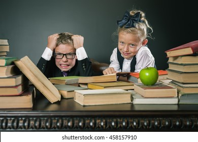 Schoolboy in stress or depression at school classroom, schoolgirl helps to boy doing many homeworks or exam. It's driving his crazy. Motivate your child to study a boring subject. Grade retention
