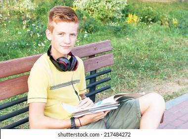 Schoolboy teen (teenager) is sitting with books, head phone on the bench in the city park. Young red-head boy is studying. Caucasian cute male model (14 year). Sunny day. Education concept. Close up.