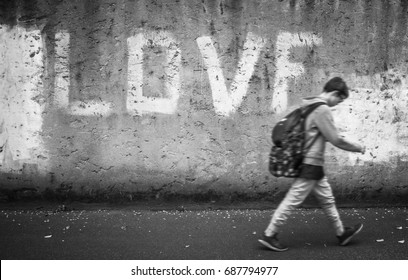 Schoolboy walking down the street with head bowed; love on background. Back to school.