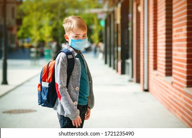 Schoolboy wearing face mask during epidemic. Back to school concept. Cute boy outside at school having good time. Safety mask to coronavirus prevention. Kid with backpack going to school. Education.
