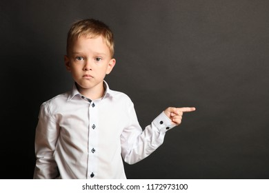 Schoolboy in white shirt shows finger on black background. Concept school.