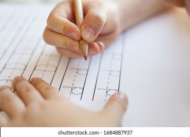 Schoolboy  writing letters. Close-up  pencil in the hand of child. Boy  learning to write letters at the table. A home distance learning.