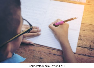schoolboy's hands with pencil writing on notebook