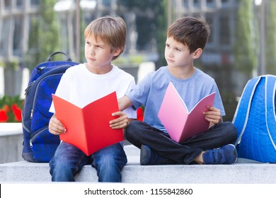 Schoolboys learning reading, doing homework after school outdoors