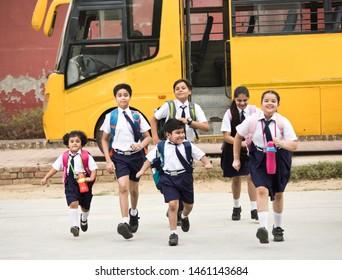 Schoolboys and schoolgirls walking of the school bus