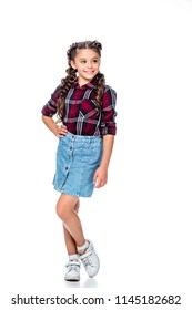 schoolchild in denim skirt and checkered shirt posing and looking away isolated on white