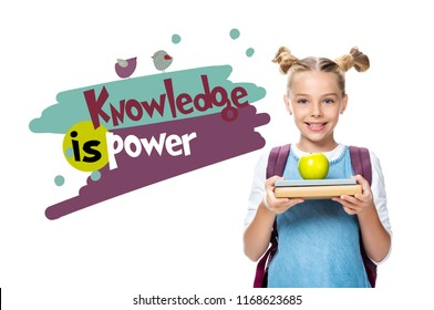 """schoolchild holding apple on books isolated on white, with """"knowledge is power"""" lettering"""