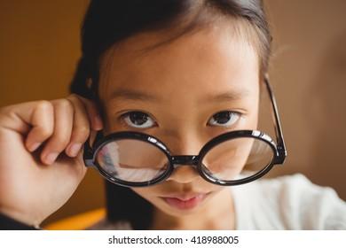 Schoolchild holding her glasses at school